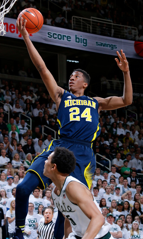 . Michigan\'s Aubrey Dawkins (24) gets a fast-break layup off a steal against Michigan State\'s Bryn Forbes during the first half of an NCAA college basketball game, Sunday, Feb. 1, 2015, in East Lansing, Mich. (AP Photo/Al Goldis)