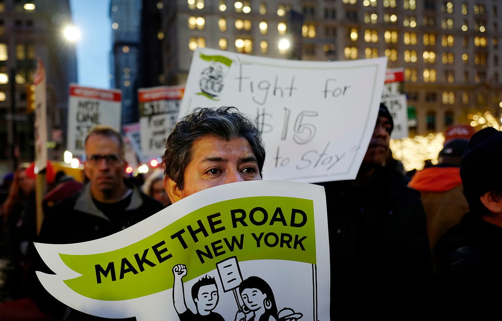 . A man holds a sign in front of his face while joining a protest in front of a McDonald\'s restaurant, Tuesday, Nov. 29, 2016, in New York. The event was part of the National Day of Action to Fight for $15. The campaign seeks higher hourly wages, including for workers at fast-food restaurants and airports. (AP Photo/Mark Lennihan)