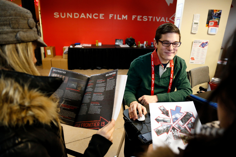 Description of . Ticket agent James Gottfredson, center, assists festival goers Taylor Humphrey, left, and Denielle Sachs, right, as they search for movies with available tickets at the box office during the 2013 Sundance Film Festival on Thursday, Jan. 17, 2013 in Park City, Utah. (Photo by Danny Moloshok/Invision/AP)