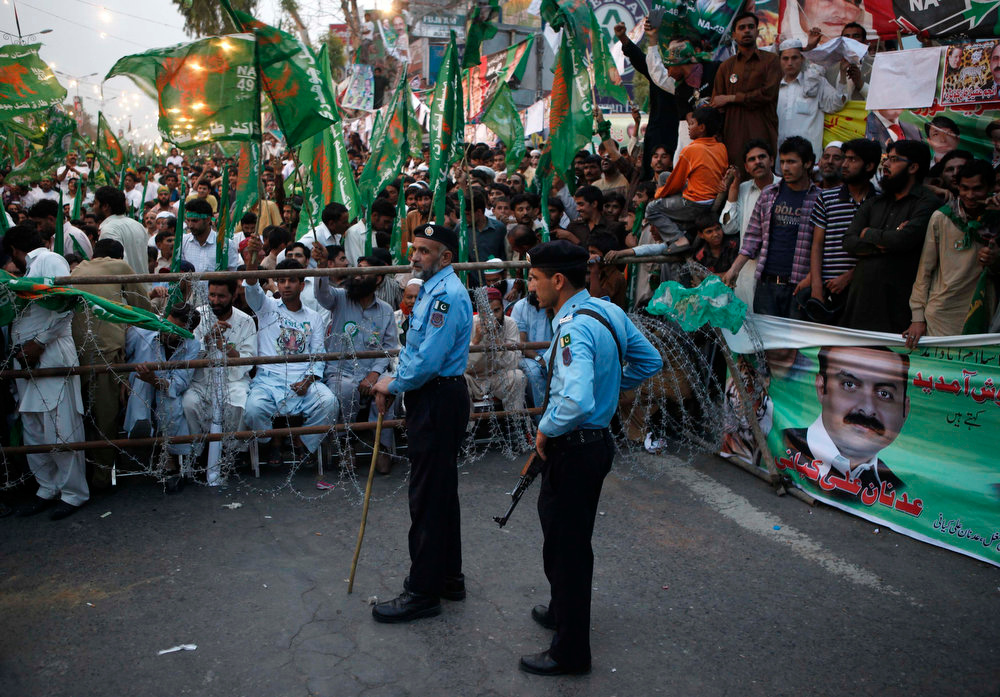 . Policemen stand guard near supporters of the Pakistan Muslim League - Nawaz (PML-N) party during an election campaign rally in Islamabad May 5, 2013. Pakistan\'s general elections will be held on May 11.  REUTERS/Mian Khursheed