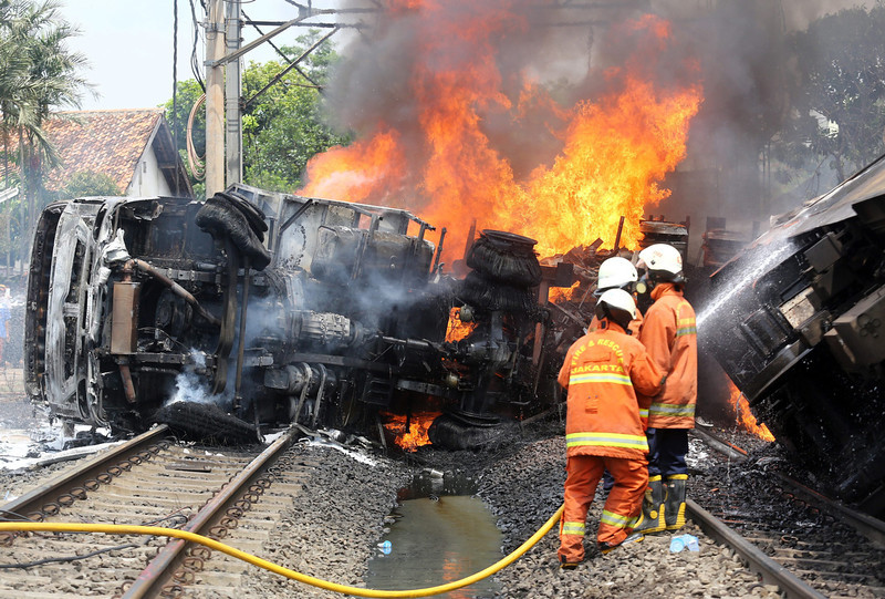 . Indonesian firefighters try to put out the fire of a collided commuter train in Jakarta, Indonesia, 09 December 2013. A commuter train ploughed into a truck carrying petrol in the Indonesian capital Jakarta, killing at least seven people and injuring more than 60, police said. The crash at a level crossing in south Jakarta sparked an explosion and sent a column of fire into the sky, television footage showed.  EPA/HERIYAWAN