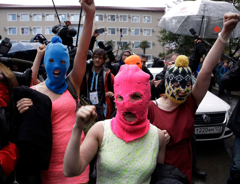. Russian punk group Pussy Riot members Nadezhda Tolokonnikova, in the blue balaclava, and Maria Alekhina, in the pink balaclava, make their way through a crowd after they were released from a police station, Tuesday, Feb. 18, 2014, in Adler, Russia. No charges were filed against Tolokonnikova and Alekhina along with the three others who were detained. (AP Photo/Morry Gash)
