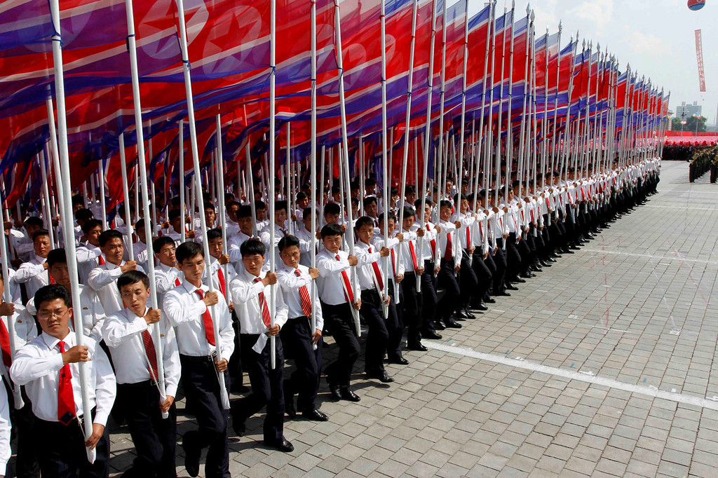 . North Koreans carry their national flag during a military parade at Kim Il Sung Square to mark the 65th anniversary of the country\'s founding in Pyongyang, North Korea, Monday, Sept. 9, 2013. (AP Photo/Kim Kwang Hyon)