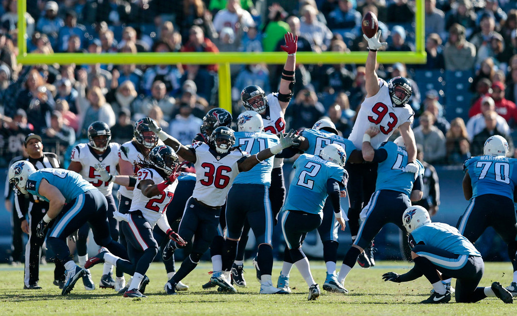 . Tennessee Titans kicker Rob Bironas (2) boots a 42-yard field goal as Houston Texans defenders D.J. Swearinger (36) and Jared Crick (93) try to block the ball in the second quarter of an NFL football game on Sunday, Dec. 29, 2013, in Nashville, Tenn. (AP Photo/Wade Payne)