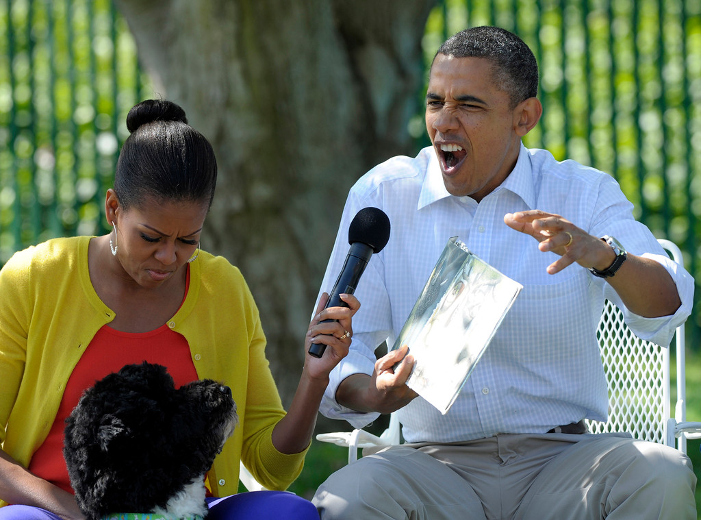 ". President Barack Obama, accompanied by first lady Michelle Obama, and first dog Bo, reads ""Where the Wild things Are\"" during the annual White House Easter Egg Roll, Monday, April 9, 2012, on the South Lawn of the White House in Washington. (AP Photo/Susan Walsh)"