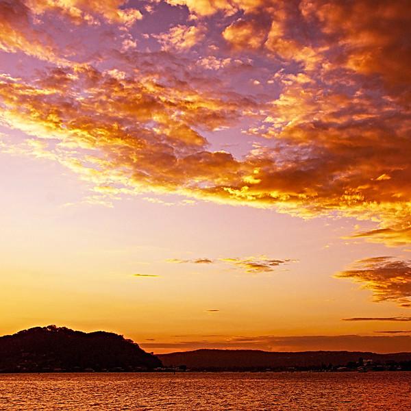 Orange colored Altocumulus cloud, sunset seascape.