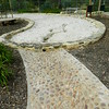 large kidney shaped sandpit with stone wall edging and pebble stream