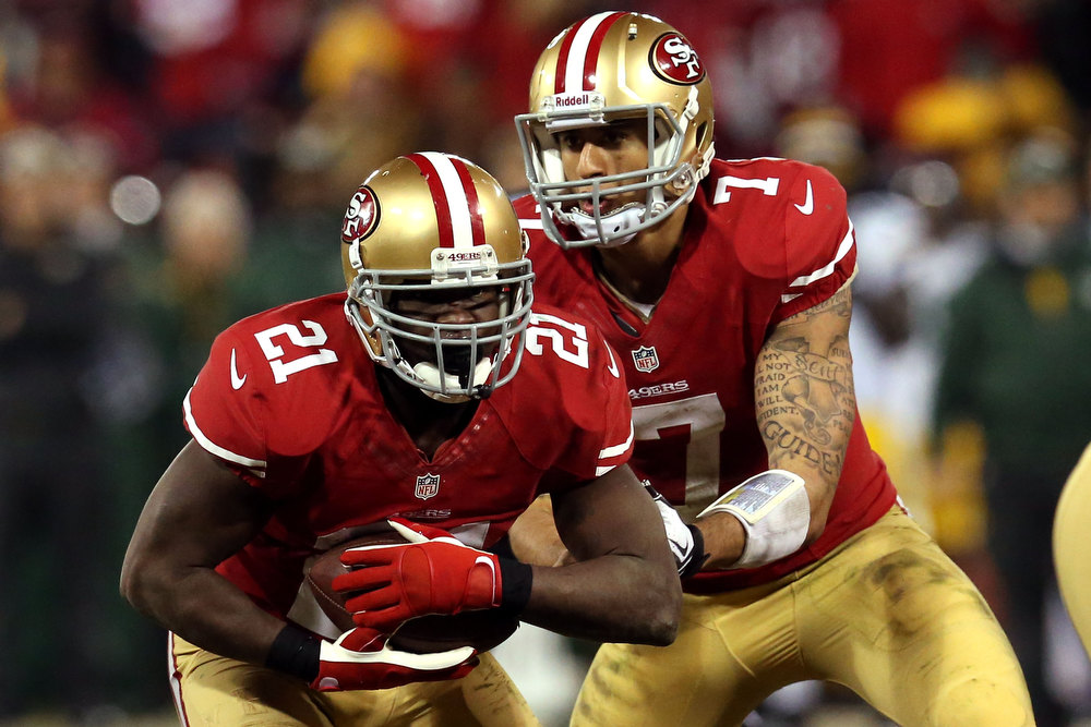 Description of . Quarterback Colin Kaepernick #7 of the San Francisco 49ers hands the ball to running back Frank Gore #21 against the Green Bay Packers during the NFC Divisional Playoff Game at Candlestick Park on January 12, 2013 in San Francisco, California.  (Photo by Stephen Dunn/Getty Images)