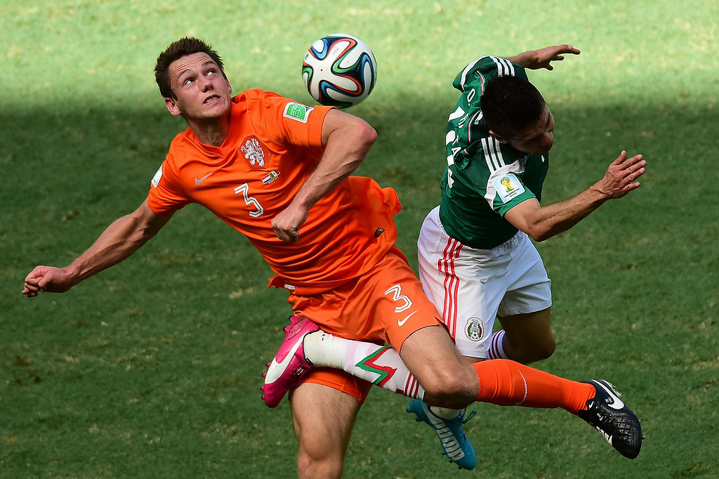 . Netherlands\' defender Stefan de Vrij (L) challenges Mexico\'s forward Oribe Peralta for the ball during a Round of 16 football match between Netherlands and Mexico at Castelao Stadium in Fortaleza during the 2014 FIFA World Cup on June 29, 2014.   JAVIER SORIANO/AFP/Getty Images