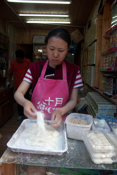 Lady making a type of candy that I used to eat while growing up.  The white stuff looks like hair and is made of candy.In the square plastic box are chopped up nuts and sesame seeds that is wrapped inside the white stringy candy.Finished product is in the clear boxes on the right that look like cocoons.