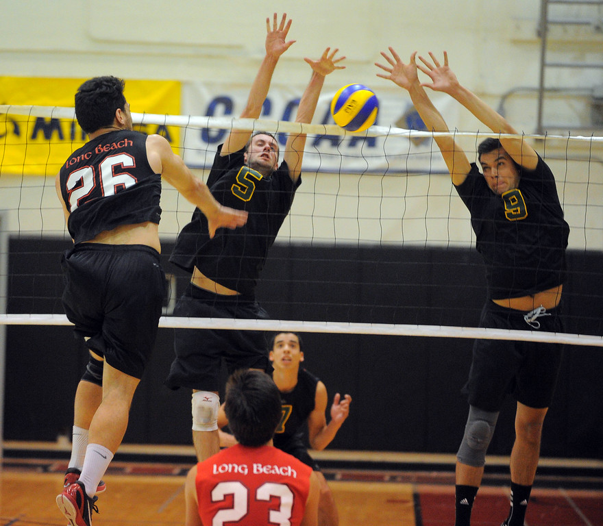 . LONG BEACH - 04/18/13 - (Photo: Scott Varley, Los Angeles Newspaper Group)  Long Beach City College vs Grossmont in the CCCAA State Volleyball semifinals. Grossmont won 3-1. Greg Utupo\'s spike is blocked by Garrett Adleman and Frank Herrera, right.