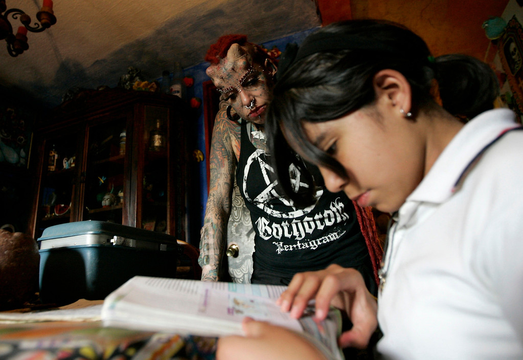 . Maria Jose Cristerna (rear) helps her daughter Samantha with her homework at their home in Guadalajara February 29, 2012.   REUTERS/Alejandro Acosta