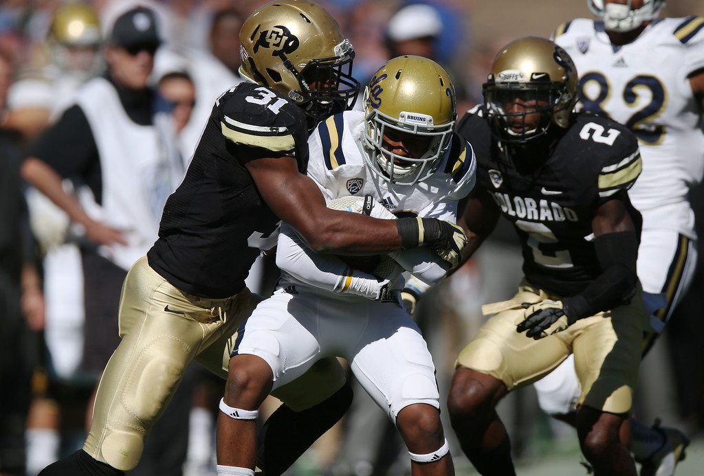 . UCLA wide receiver Ahmaad Harris, center, is stopped after catching pass for short gain by Colorado outside linebacker Kenneth Olugdobe, left, and defensive back Ken Crawley in the first second quarter of an NCAA football game in Boulder, Colo., on Saturday, Oct. 25, 2014. (AP Photo/David Zalubowski)