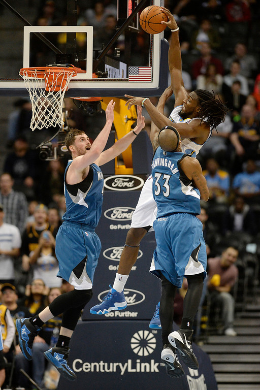 . Dante Cunningham (33) of the Minnesota Timberwolves fouls Kenneth Faried (35) of the Denver Nuggets as Kevin Love (42) of the Minnesota Timberwolves gives help on the defensive effort during the second half of the Timberwolves\' 132-128 win. (Photo By AAron Ontiveroz/The Denver Post)