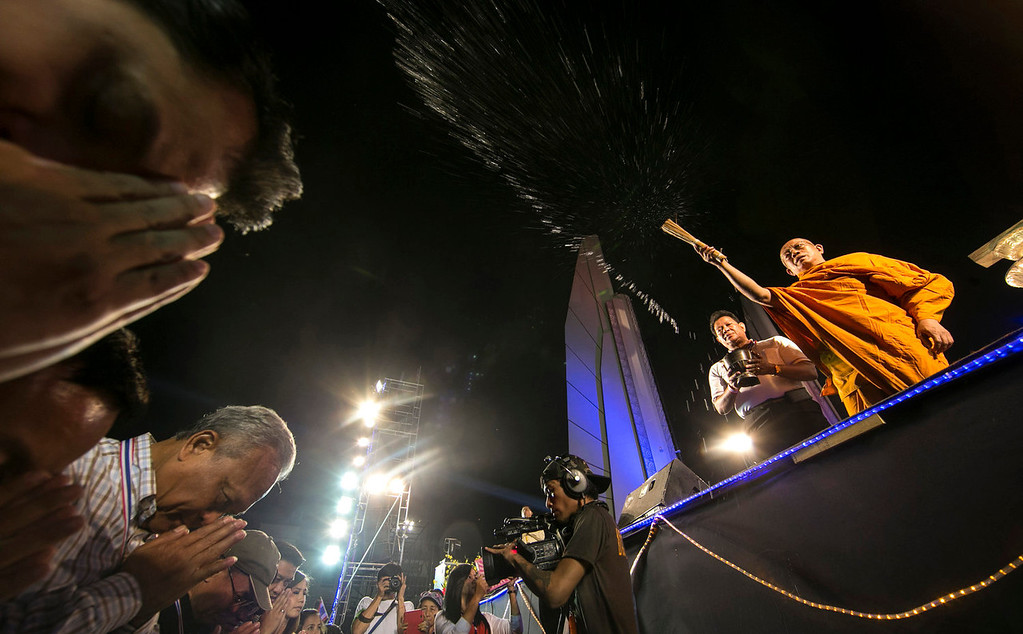. Anti-government protest leader Suthep Thaugsuban, bottom left, gets a blessing from a Buddhist monk who splashes him with holy water during a New Year celebration at the Democracy Monument in Bangkok, Thailand, Wednesday, Jan. 1, 2014 . (AP Photo/Wason Wanichakorn)
