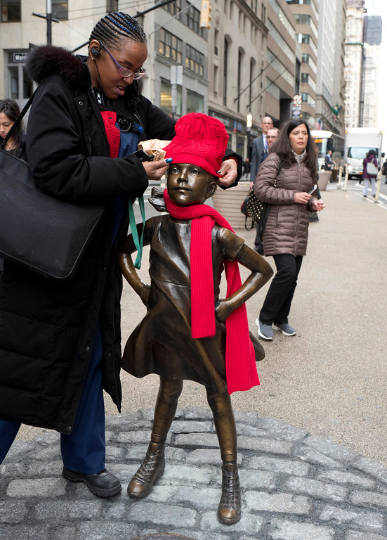 ". Haroldlynn Hill-Williams places her red hat on a statue of a fearless girl, Wednesday, March 8, 2017, in New York. The statue was installed by an investment firm in honor of International Women\'s Day. An inscription at the base reads, ""Know the power of women in leadership. She makes a difference. State Street Global Advisors.\"" (AP Photo/Mark Lennihan)"