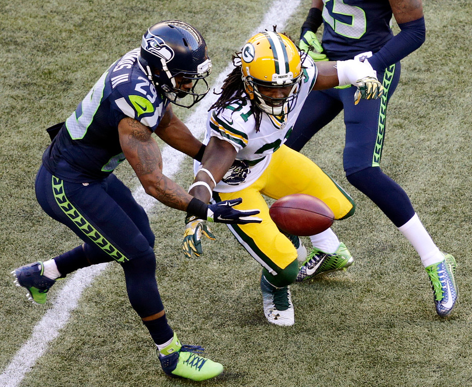 . Seattle Seahawks\' Earl Thomas, left, muffs the catch on a punt as Green Bay Packers\' Davon House reaches for the ball in the first half of an NFL football game, Thursday, Sept. 4, 2014, in Seattle. The Seahawks got possession. (AP Photo/Scott Eklund)