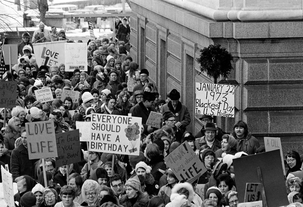 """. An estimated 5,000 people, women and men, march around the Minnesota Capitol building protesting the U.S. Supreme Court\'s Roe v. Wade decision, ruling against state laws that criminalize abortion, in St. Paul, Minn., Jan. 22, 1973.  The marchers formed a \""""ring of life\"""" around the building.  (AP Photo)"""