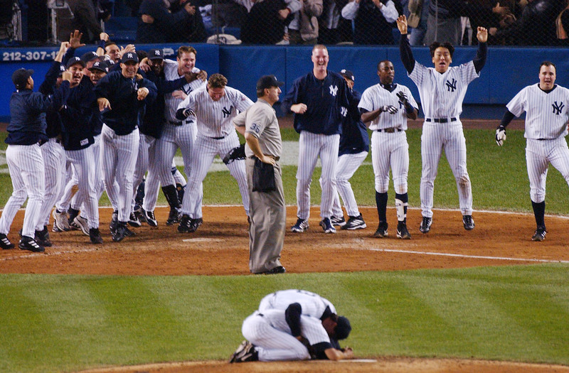 . The New York Yankees celebrate in the eleventh inning as they await Aaron Boone (not shown) circling the bases after beating the Boston Red Sox in Game 7 of the American League Championship Series Thursday, Oct. 16, 2003 in New York. The Yankees won 6-5. Yankees pitcher Mariano Rivera, foreground, is consoled by an unidentified teammate as he kneels on the mound in celebration. (AP Photo/Bill Kostroun)