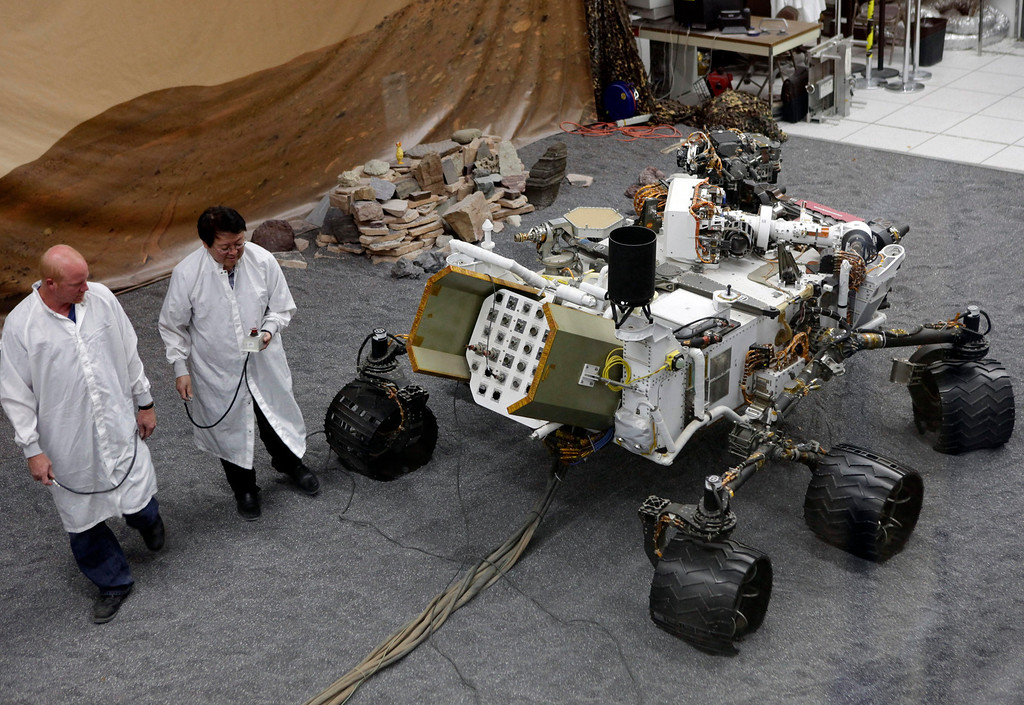 . FILE - In this Thursday, Aug. 2, 2012 file photo, engineers work on a model of the Mars rover Curiosity at the Spacecraft Assembly Facility at NASA\'s Jet Propulsion Laboratory in Pasadena, Calif. (AP Photo/Damian Dovarganes)