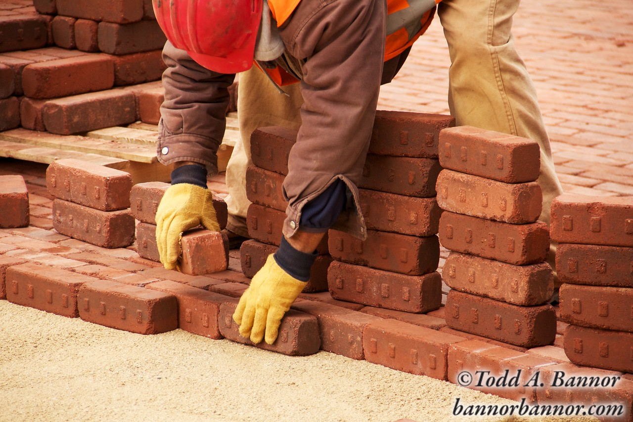 A construction worker lays paving bricks during Marion Street reconstruction project on Saturday November 19, 2011 in Oak Park, Illinois, USA.  Brick is being used to return the street to its early 20th century appearance and reduce storm runoff.