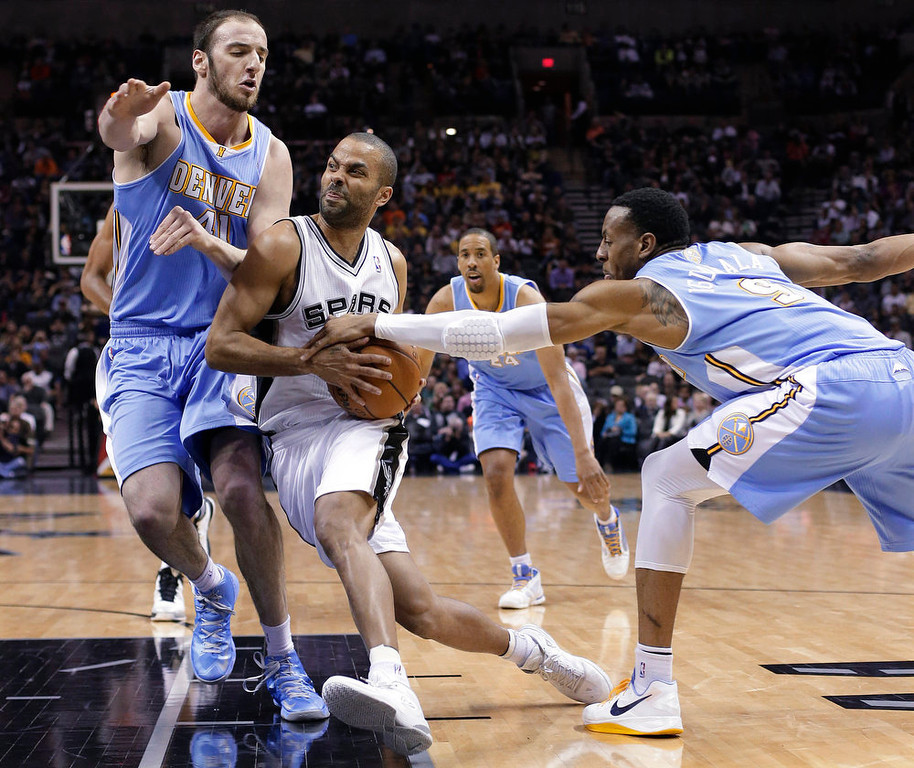 . San Antonio Spurs\' Tony Parker, center, of France, drives between Denver Nuggets defenders Kosta Koufos (41) and Andre Iguodala (9) during the first half of an NBA basketball game, Wednesday, March 27, 2013, in San Antonio. (AP Photo/Eric Gay)