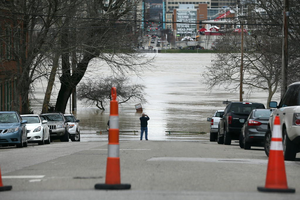 . A man takes a picture of flood waters at the intersection of Riverside Drive and Garrard Street, Sunday, Feb. 25, 2018, in Covington, Ky. The weather service said moderate flooding was expected along the Ohio River in Kentucky and Ohio, including in Cincinnati, where the river was 8 feet above flood stage Sunday. (Kareem Elgazzar/The Cincinnati Enquirer via AP)