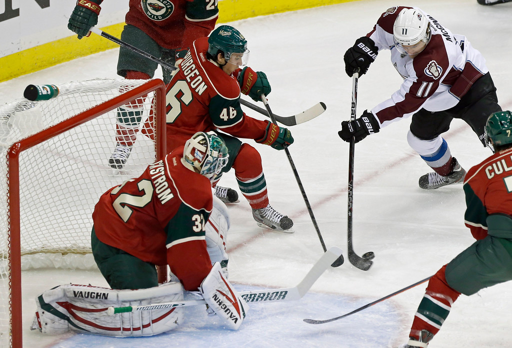 . Minnesota Wild goale Niklas Backstrom of Finland, left, and Jared Spurgeon (46) stop a scoring attempt by Colorado Avalanche\'s Jamie McGinn, right, in the first period of an NHL hockey game Saturday, Jan. 19, 2013 in St. Paul, Minn. (AP Photo/Jim Mone)