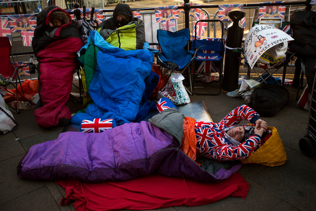 . A man sleeps on the ground, spending the night near Windsor castle, England, Friday, May 18, 2018. Preparations continue in Windsor ahead of the royal wedding of Britain\'s Prince Harry and Meghan Markle Saturday, May 19. (AP Photo/Emilio Morenatti)
