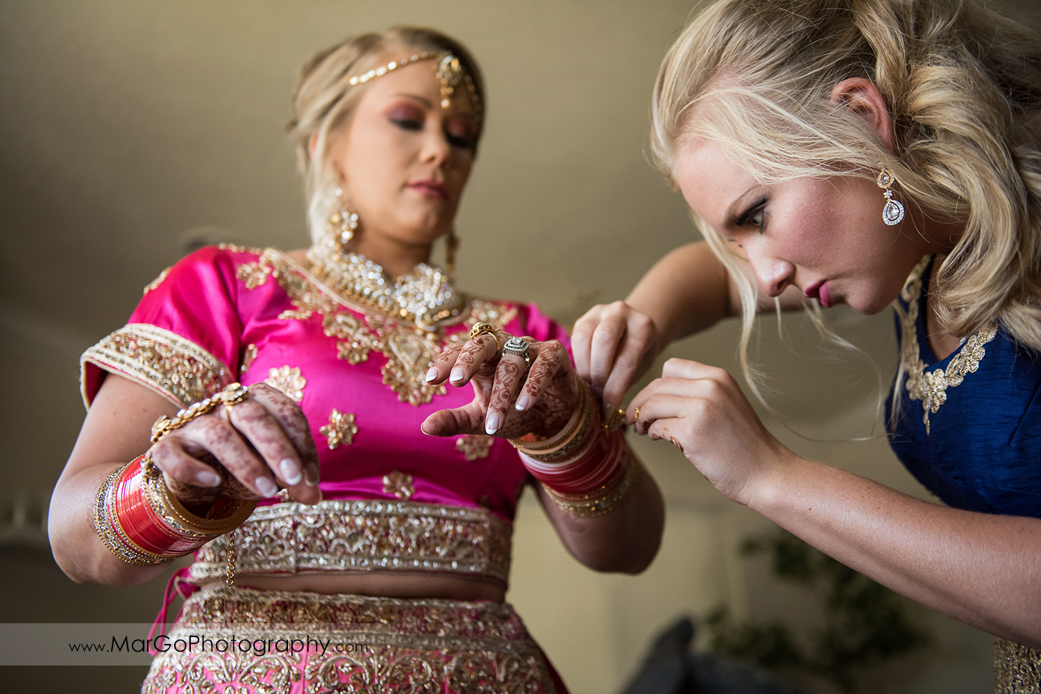 Indian bride preparation - putting on golden hand jewelry
