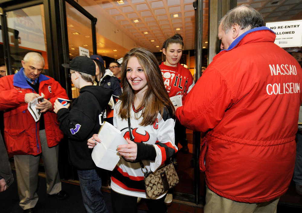 Description of . A smiling New Jersey Devils fan enters the Nassau Coliseum for the Devils versus the New York Islanders NHL hockey game for the opening of NHL hockey season on Saturday Jan., 19, 2013 at Nassau Coliseum  in Uniondale, N.Y. (AP Photo/Kathy Kmonicek)