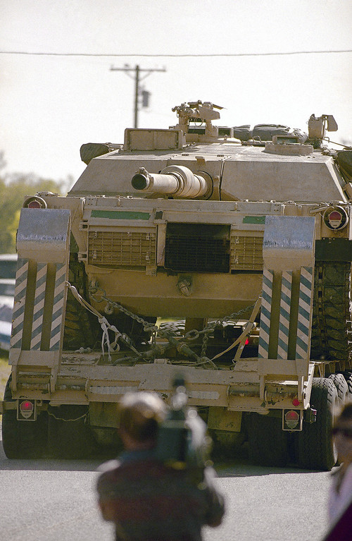 . A television cameraman films an armored vehicle loaded on a truck passing the media checkpoint as a convoy departs from the remains of the Branch Davidian compound in Waco, Texas on Tuesday, April 20, 1993. Armored vehicles were used in a tactical maneuver Monday on the religious cult\'s fortification. (AP Photo)