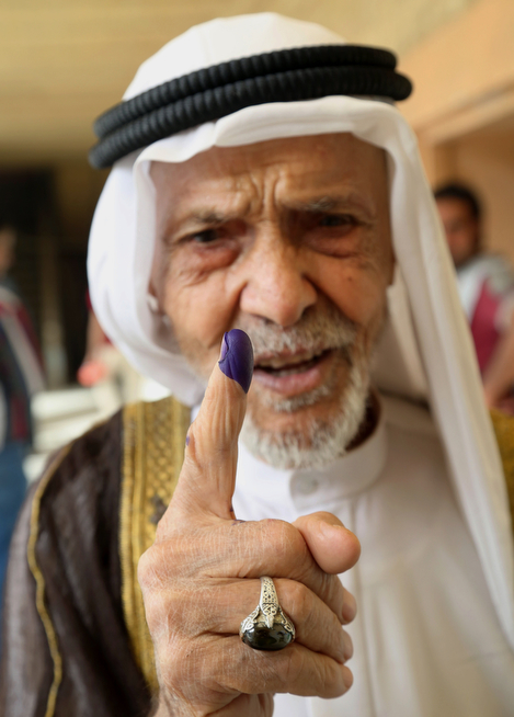 Description of . An elderly Iraqi man shows his ink-stained finger after casting his vote at a polling center in Basra, Iraq's second-largest city, 340 miles (550 kilometers) southeast of Baghdad, Iraq, Wednesday, April 30, 2014. Iraq is holding its third parliamentary elections since the U.S.-led invasion that toppled dictator Saddam Hussein. More than 22 million voters are eligible to cast their ballots to choose 328 lawmakers out of more than 9,000 candidates. (AP Photo/ Nabil al-Jurani)