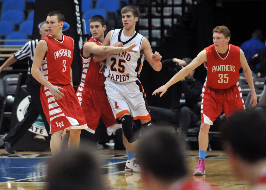 . Grand Rapid\'s star Alex Illikainen in white is guarded closely by Lakeville North  in the second  half.  (Pioneer Press: Scott Takushi)