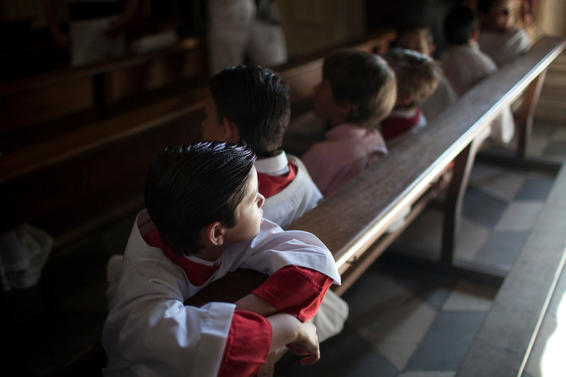 Altar boys looking at the Corpus Christi procession, Seville, Spain, 2009.