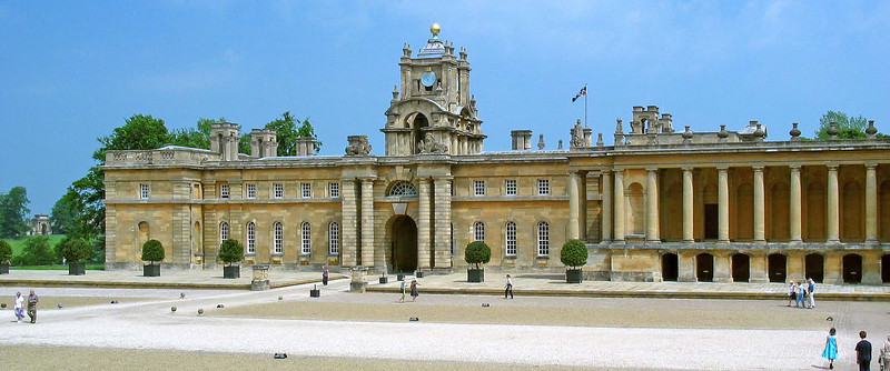 """Blenheim Palace side facade  Blenheim Palace is a large and monumental country house situated in Woodstock, Oxfordshire, England. It is the only non-episcopal country house in England to hold the title """"palace"""".  The Palace, one of England's largest houses, was built between 1705 and circa 1724. It was recognised as a UNESCO World Heritage Site in 1987. Its construction was originally intended to be a gift to John Churchill, the 1st Duke of Marlborough from a grateful nation in return for military triumph against the French and Bavarians.   However, it soon became the subject of political infighting, which led to Marlborough's exile, the fall from power of his Duchess, and irreparable damage to the reputation of the architect Sir John Vanbrugh. Designed in the rare, and short-lived, English baroque style, architectural appreciation of the palace is as divided today as it was in the 1720s.  It is unique in its combined usage as a family home, mausoleum and national monument. The palace is also notable as the birthplace and ancestral home of Prime Minister Sir Winston Churchill."""