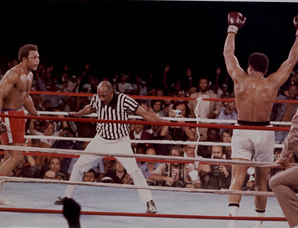. Muhammad Ali, arms raised in victory, walks to his corner as referee Zack Clayton counts out George Foreman after Ali knocked him down in the eighth round of their title bout in Kinshasa, Zaire, Oct. 29, 1974. (AP Photo)