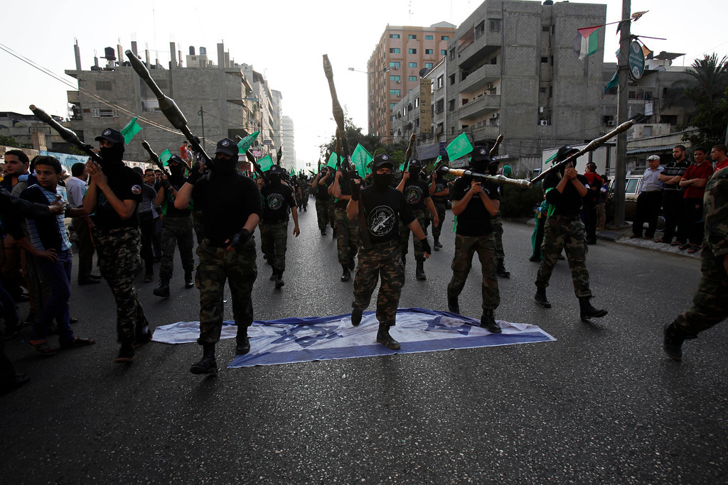 . Masked Palestinian members of the Ezz Al-Din Al Qassam brigade, the military wing of Hamas, step on a representation of the Israeli flag while marching during a parade to mark the anniversary of a battle against Israel in Gaza City, Thursday, Nov. 14, 2013.  (AP Photo/Adel Hana)