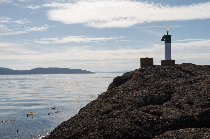A channel marker light sits atop the rocky shore in the Gulf Islands