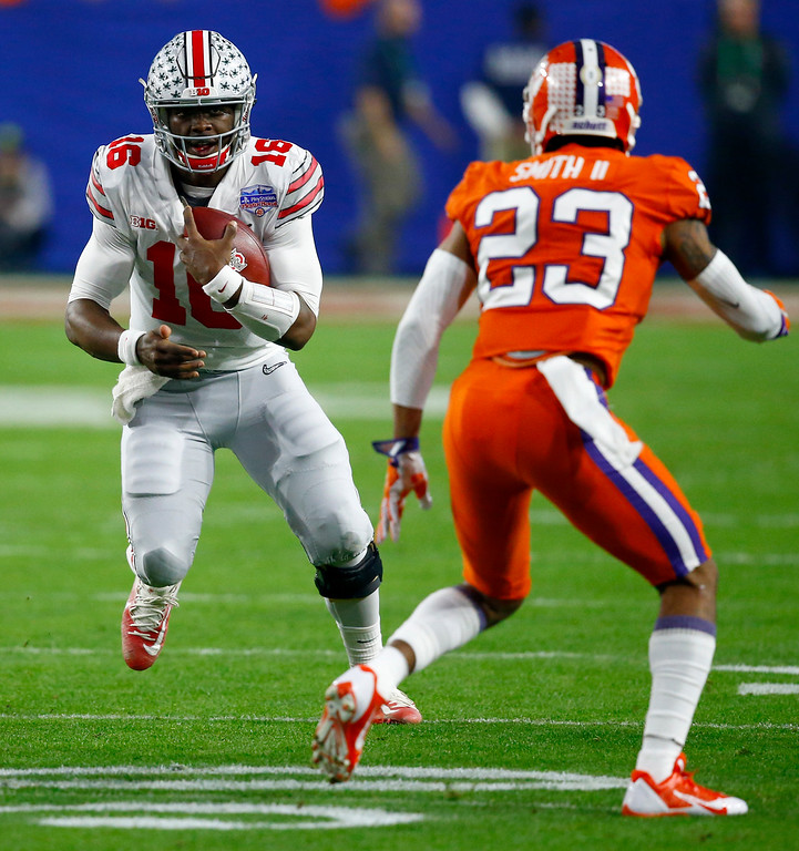 . Ohio State quarterback J.T. Barrett (16) runs as Clemson safety Van Smith (23) pursues during the first half of the Fiesta Bowl NCAA college football game, Saturday, Dec. 31, 2016, in Glendale, Ariz. (AP Photo/Ross D. Franklin)