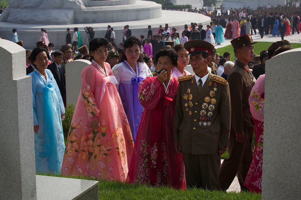. North Korean brother and sister Pak Yun Yong, front right, and Pak Chun Son, wiping her eyes with handkerchief at center, visit the grave of their Korean War veteran father Pak Hyon Jong who died in 1953 when the son was 8 and the daughter was 5 years old. North Korea opened a cemetery for Korean War veterans on Thursday, July 25, 2013 in Pyongyang, North Korea marking the 60th anniversary of the signing of the armistice that ended hostilities on the Korean peninsula. (AP Photo/David Guttenfelder)
