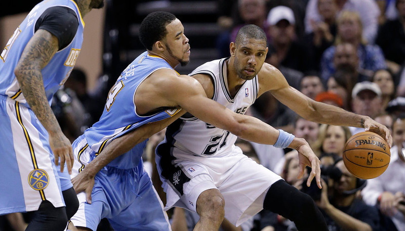 . San Antonio Spurs\' Tim Duncan (21) is pressured by Denver Nuggets\' JaVale McGee, center, during the second half of an NBA basketball game, Wednesday, March 27, 2013, in San Antonio. San Antonio won 100-99. (AP Photo/Eric Gay)