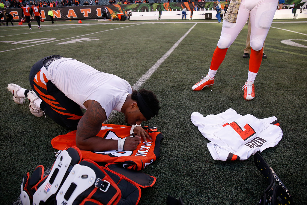 . Cincinnati Bengals running back Joe Mixon, left, signs his jersey before exchanging with Cleveland Browns quarterback DeShone Kizer (7) after an NFL football game, Sunday, Nov. 26, 2017, in Cincinnati. (AP Photo/Gary Landers)