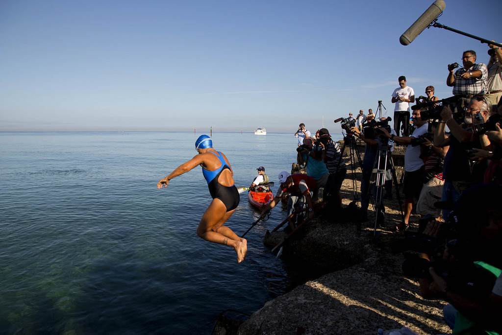 . U.S. swimmer Diana Nyad, 64, jumps into the water to begin her swim to Florida from the waters off Havana, Cuba, Saturday, Aug. 31, 2013. Endurance athlete Nyad launched another bid Saturday to set an open-water record by swimming from Havana to the Florida Keys without a protective shark cage.   (AP Photo/Ramon Espinosa)