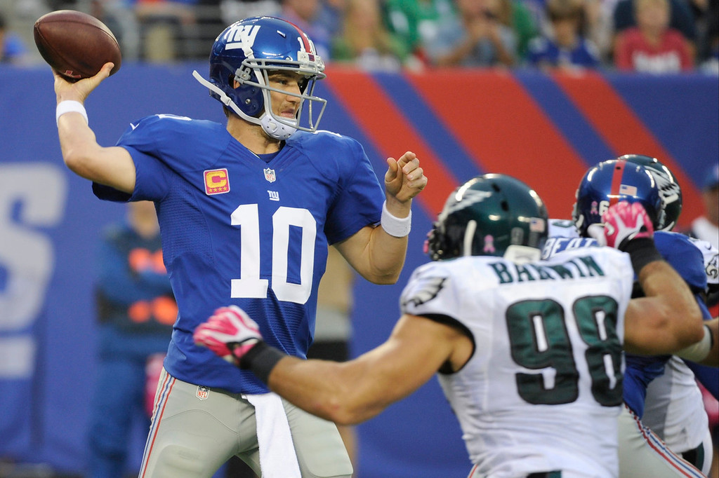 . New York Giants\' Eli Manning (10) throws a pass as Philadelphia Eagles\' Connor Barwin (98) rushes during the first half of an NFL football game on Sunday, Oct. 6, 2013, in East Rutherford, N.J. (AP Photo/Bill Kostroun)