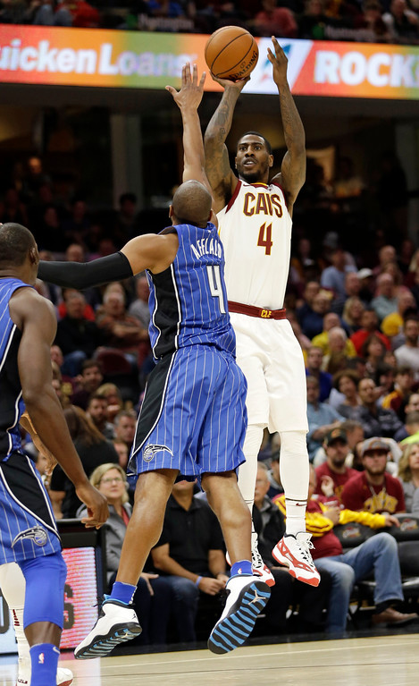 . Cleveland Cavaliers\' Iman Shumpert, back, shoots over Orlando Magic\'s Arron Afflalo in the first half of an NBA basketball game, Saturday, Oct. 21, 2017, in Cleveland. (AP Photo/Tony Dejak)