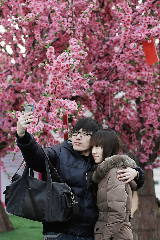 . A couple takes a picture of themselves on Valentine\'s Day February 14, 2013 in Beijing, China. Young Chinese couples have embraced the Western concept of Valentine\'s Day with hawkers selling roses and chocolates.(Photo by Lintao Zhang/Getty Images)