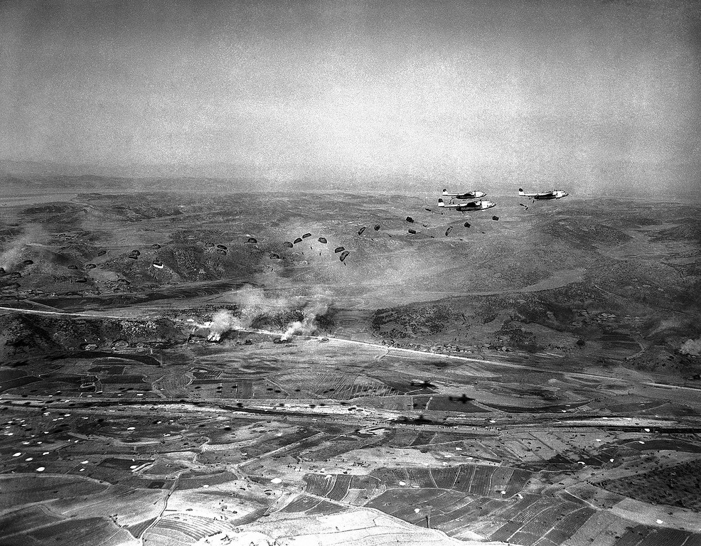 . Paratroopers spill out of flying boxcars planes over Munsan sector in Korea on March 23, 1951 in mass airdrop behind enemy lines North of Seoul. Dwellings on ground still burning after pre-invasion shelling. (AP Photo/James Martenhoff
