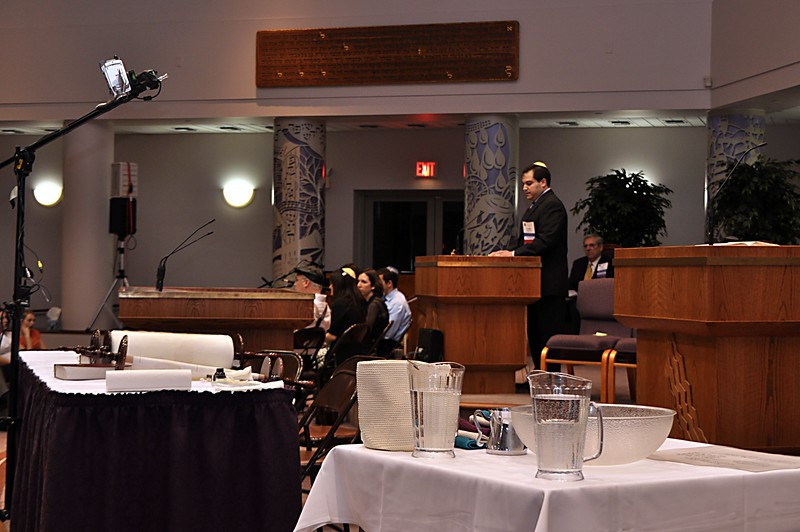 Craig gives opening remarks.  The setup for the final fill-ins is visible in the foreground.  The camera mounted above the Torah scroll was used to project a closeup of the fill-ins for the congregation to see. (photo by Sam Backman)