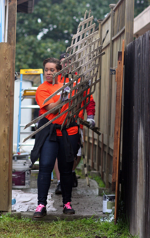 . Martesha Williams, of Tracy, a volunteer with Home Depot, removes debris from the home of Navy veteran Joseph Catalano in Hayward, Calif., on Thursday, Jan. 24, 2013. The Columbus, Ga. nonprofit House of Heroes is partnering with Home Depot to repair 36 houses owned by military and public safety veteran or their spouses around the nation. (Anda Chu/Staff)